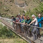 Group crossing a suspension bridge over a river • Bhutan Within The Frame 2017 • photo: Marek Pleszczynski